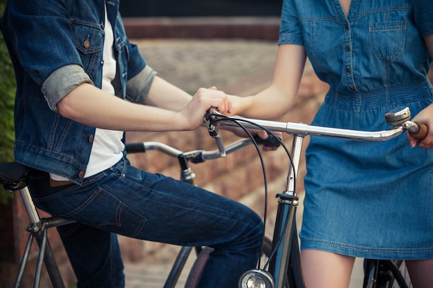 Молодая пара сидит на велосипеде напротив города