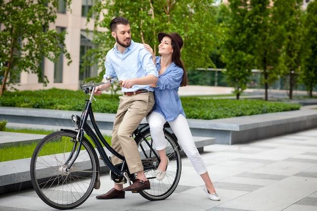 Молодая пара сидит на велосипеде