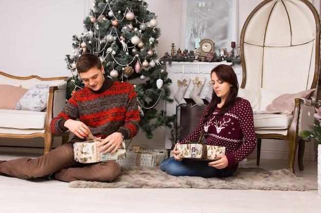 装飾された暖炉の前の敷物の上に座っている若いカップルと笑顔でクリスマスプレゼントを開梱するクリスマスツリー