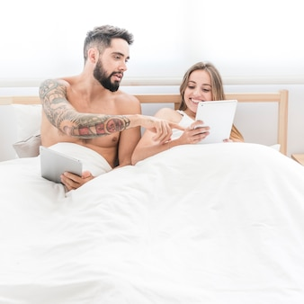 Young couple sitting on bed using cellphone