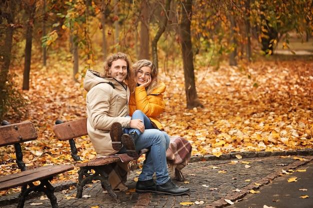 Молодая пара, сидя на скамейке в осеннем парке