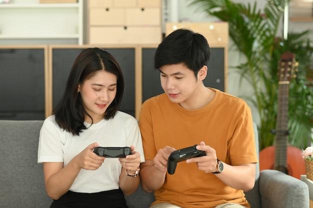 ソファに座ってジョイスティックを使って一緒にゲームをする若いカップル。