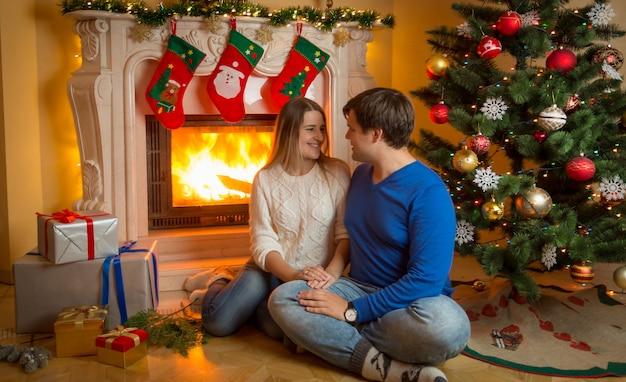 燃える暖炉の床に座ってクリスマスプレゼントを贈る若いカップル