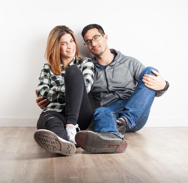 若いカップル微笑床に座っ