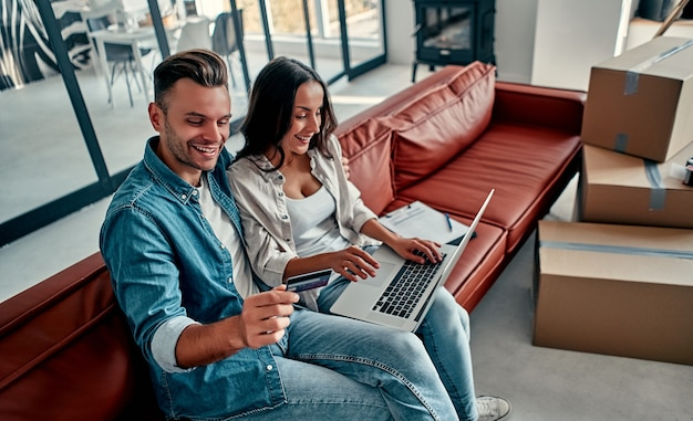 새 집으로 이사하는 동안 컴퓨터 무선 인터넷과 신용 카드를 사용하여 바닥에 함께 앉아 있는 젊은 부부. 이사, 집 구입, 아파트 개념.