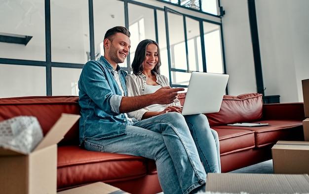 새 집으로 이사하는 동안 컴퓨터 무선 인터넷을 사용하여 함께 바닥에 앉아 있는 젊은 부부. 이사, 집 구입, 아파트 개념.