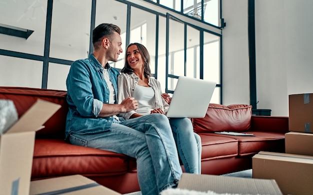 Молодая пара, сидя на полу вместе с помощью компьютера беспроводной интернет при переезде в новый дом. переезд, покупка дома, концепция квартиры.