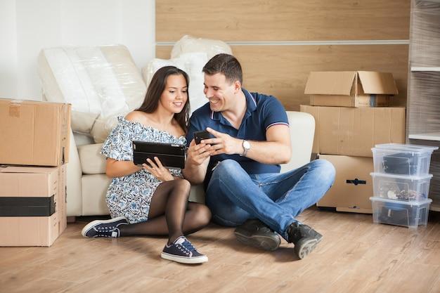床に座っている若いカップル。彼らの新しい家に引っ越した後、タブレットコンピュータを使用して床に座っている若いカップル