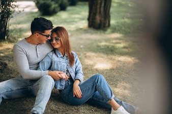 Young couple sitting on grass in park