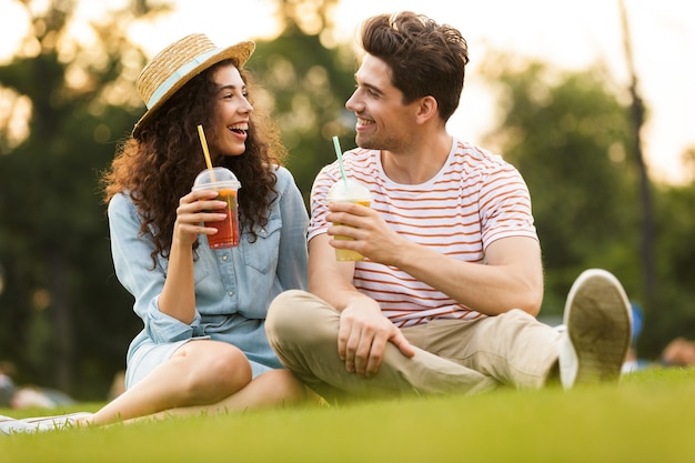 Молодая пара сидит на зеленой траве в парке и пьет напитки из пластиковых стаканчиков