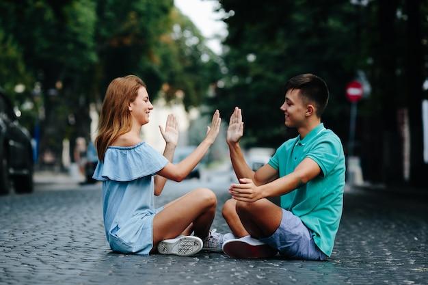 Молодая пара, сидя на дороге играет