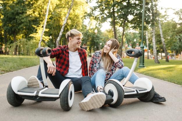 Молодая пара, сидя на дороге с гироскопом в летнем парке