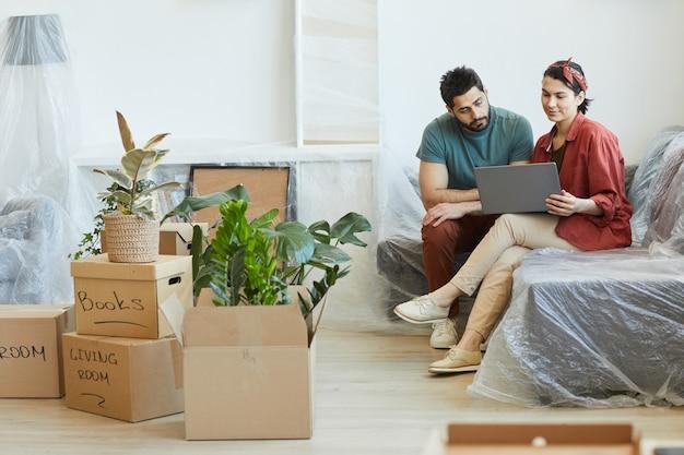 物が入った箱の中でソファに座って、新しいアパートでラップトップコンピューターを使用している若いカップル
