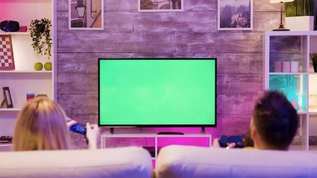 젊은 부부는 소파에 앉아 녹색 화면으로 tv에서 온라인 게임을 하고 있습니다. 행복한 관계. 게이머 커플.