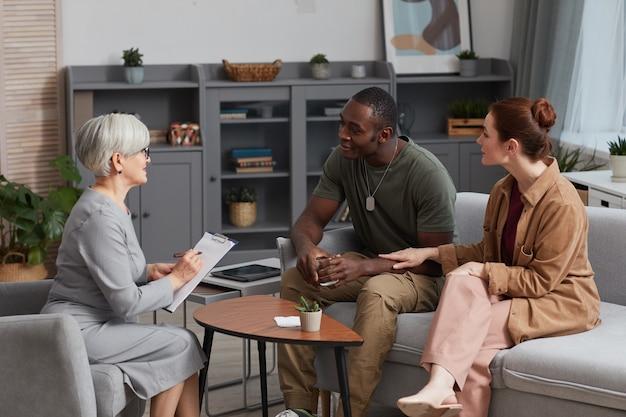 ソファに座って、訪問中に家族心理学者と話している若いカップル