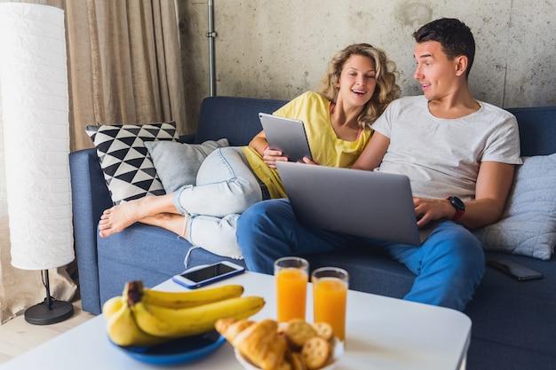 Молодая пара, сидя на диване у себя дома, глядя в ноутбук