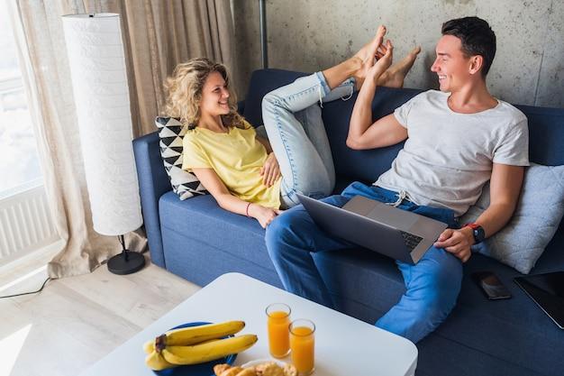 Молодая пара, сидя на диване у себя дома с помощью ноутбука