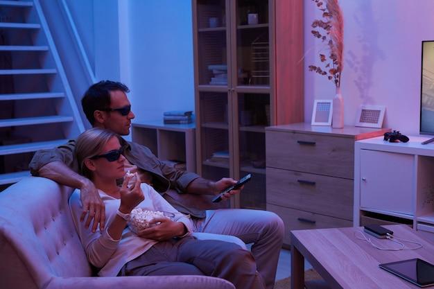 3d 안경에 소파에 앉아 어두운 거실에서 tv를 보는 젊은 부부
