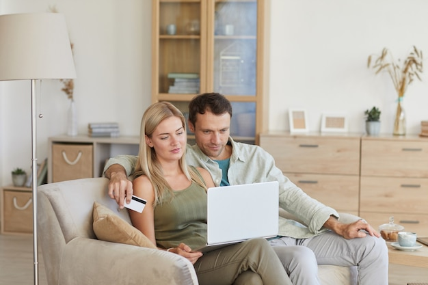 彼らはオンラインで買い物をし、リビングルームでクレジットカードを使用してラップトップでソファに座っている若いカップル
