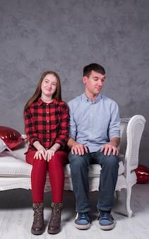 Молодая пара, сидя на диване