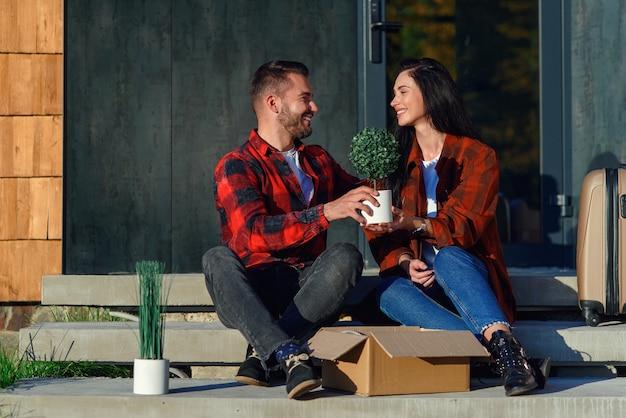新しい家に引っ越した後、箱を開梱するのを楽しんでいる階段に座っている若いカップル。