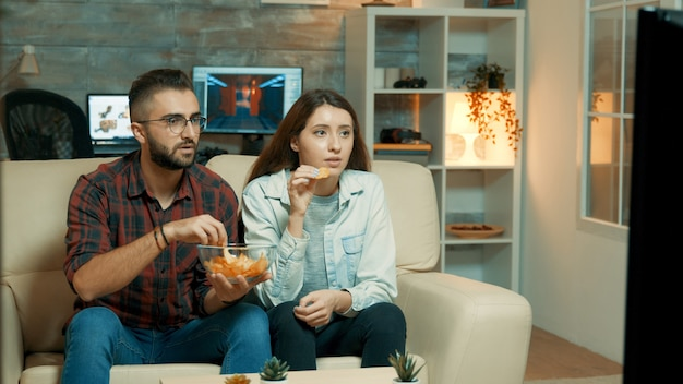 ソファに座って、チップを楽しんでいるテレビを見ている若いカップル。テレビで緊張しているカップル。