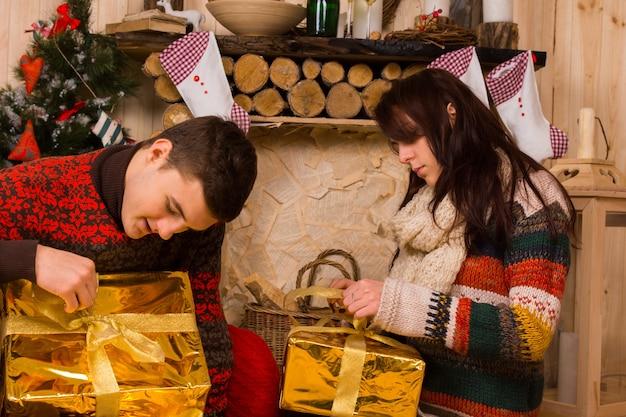 素朴なキャビンの床に座って、熱心な期待を持ってお祝いのゴールドのクリスマスプレゼントを開く若いカップル
