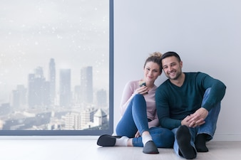 Young couple sitting on the floor near window at home