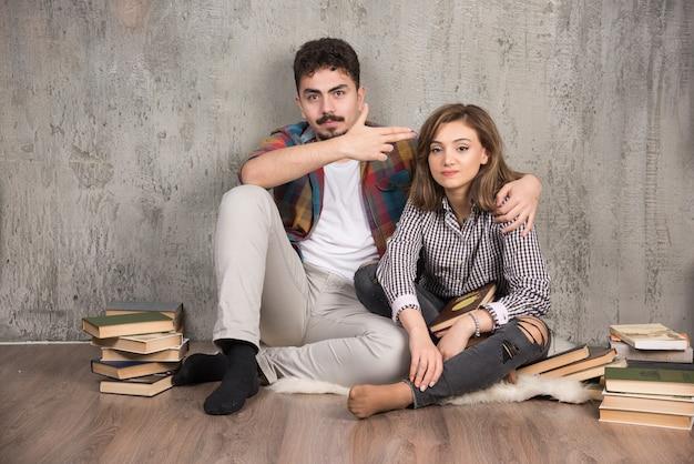 本と床に座っている若いカップル