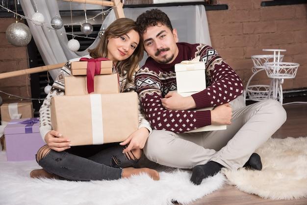クリスマスのインテリアでボックスギフトと床に座っている若いカップル。