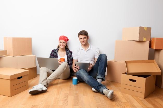 ボックスと床に座って、ラップトップとタブレットを使用して若いカップル