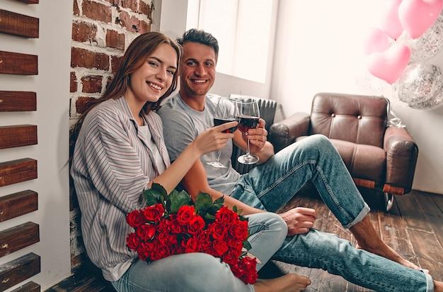 와인과 빨간 장미의 안경 바닥에 앉아 젊은 부부