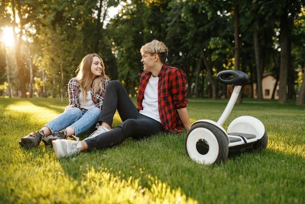 Молодая пара, сидя на траве возле гироскопа в летнем парке
