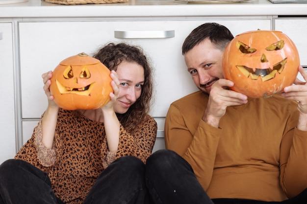 Молодая пара сидит на полу кухни и держит тыквы на хэллоуин