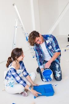 Молодая пара сидит на белом полу и наливает краску