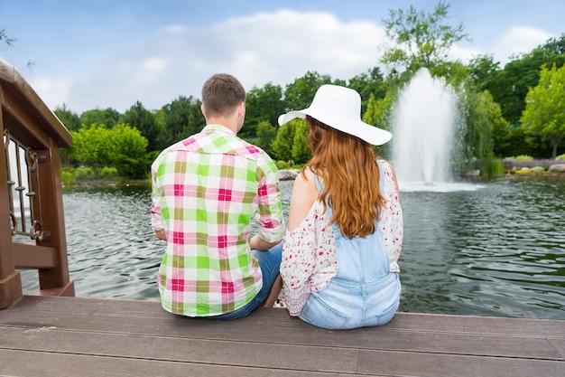 나무 데크에 앉아 분수와 다른 나무가 있는 공원 연못에서 오리에게 먹이를 주는 젊은 부부
