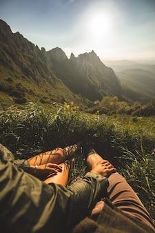 山の頂上に座って、日没時に景色を楽しむ若いカップル