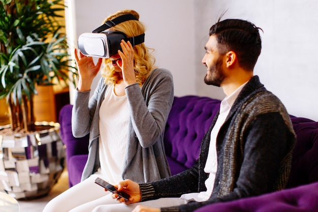 Young couple sitting in the room while young woman has a virtual reality glasses