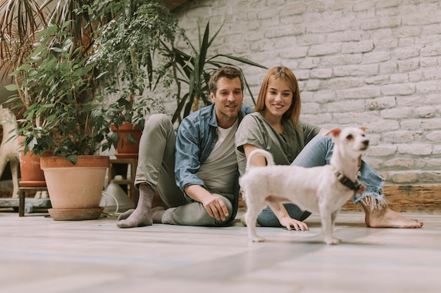 Young couple sitting at rustic living room floor and playing with dog