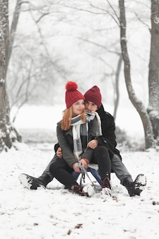 Young couple sitting on sleigh in winter daylight