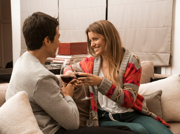 Young couple sitting on sofa enjoying the drink