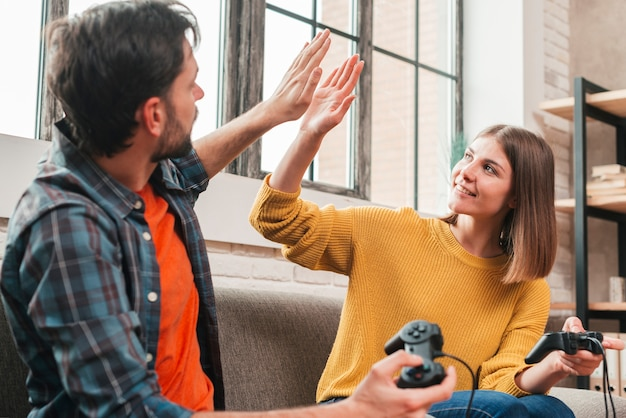 Young couple sitting on sofa holding joystick giving high-five