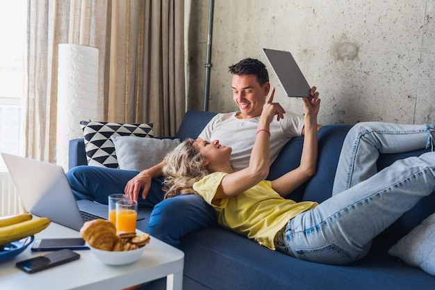 Young couple sitting on sofa at home looking in tablet, watching online