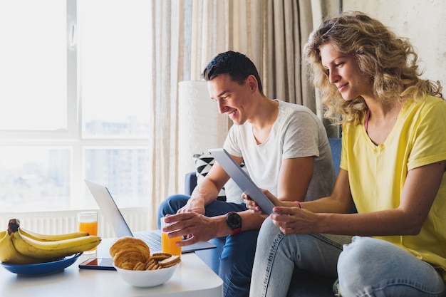 Young couple sitting on sofa at home working online on laptop and tablet