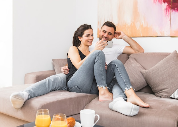 Young couple sitting on sofa watching video on mobile phone at home