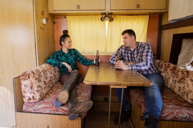 Young couple sitting at table in campervan talking about something. drink beer