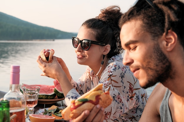 Young couple sitting at the table eating hot dogs on the nature outdoors