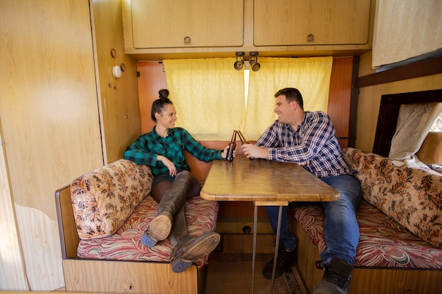 Young couple sitting at table in retro camper and clicking beer. relax atmosphere