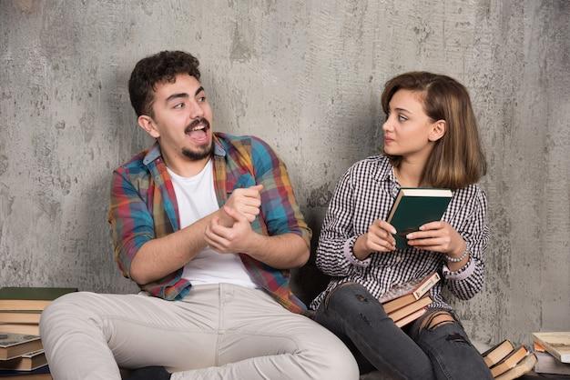Giovane coppia seduta e prendendo un libro gli uni dagli altri