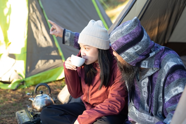 Young couple sitting in the tent and drinking coffee in the morning